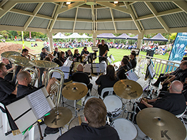 A brass band playing on an outdoor stage.