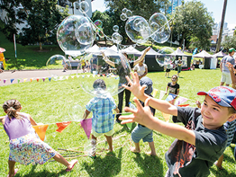 Children playing with bunting and bubbles at an outdoor park setting.