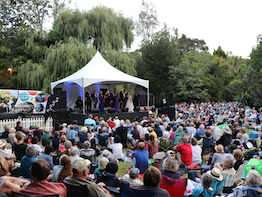 NZ Opera members singing on an outdoor stage in front of a crowd.